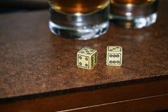 Vetri di vetro e dei dadi su un bordo di legno Fotografie Stock
