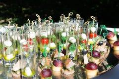 Vetri di vetro I vetri sono riempiti di spuntini: pomodoro ciliegia, mozzarella Fotografia Stock
