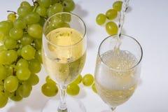 Vetri di vino bianco ed uva fresca Immagini Stock