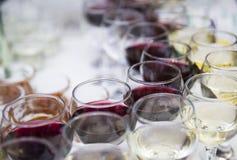 Vetri di vino con vino rosso bianco e sulla tavola sull'vaga Immagini Stock