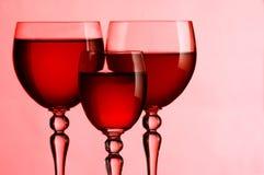 Vetri di vino con vino su un colore rosa Immagini Stock Libere da Diritti