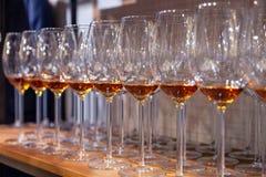 Vetri di vino del primo piano con il supporto del cognac nella fila sugli scaffali di legno Vista laterale Concetto degli alcooli immagini stock