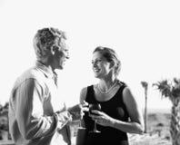 Vetri di vino della holding delle coppie. Fotografia Stock