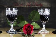 Vetri di vino e della rosa rossa che riposano sulla chitarra acustica con il segno R Immagine Stock