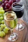 Vetri di vino rosso bianco e, uva fresca su un bordo di legno Immagini Stock