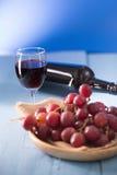 Vetri di vino rosso con l'uva rossa e una bottiglia di vino sul blu Immagini Stock Libere da Diritti
