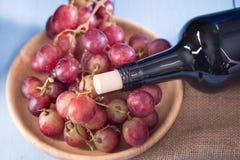 Vetri di vino rosso con l'uva rossa e una bottiglia di vino sul blu Immagini Stock