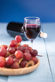 Vetri di vino rosso con l'uva rossa e una bottiglia di vino sul blu Fotografie Stock