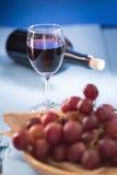 Vetri di vino rosso con l'uva rossa e una bottiglia di vino sul blu Immagine Stock Libera da Diritti