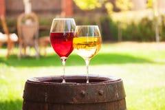 Vetri di vino rosso e bianco con l'uva sul vecchio barilotto di vino fuori Immagini Stock