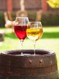 Vetri di vino rosso e bianco con l'uva sul vecchio barilotto di vino fuori Immagine Stock