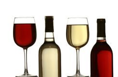 Vetri di vino rosso e bianco, con le bottiglie di vino rosso e bianco Fotografia Stock Libera da Diritti