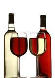 Vetri di vino rosso e bianco, con le bottiglie di vino rosso e bianco dietro Immagini Stock