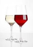 Vetri di vino rosso e bianco su bianco Immagini Stock