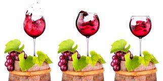 Vetri di vino rosso su un barilotto di legno con l'uva Fotografia Stock