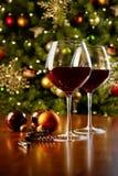 Vetri di vino rosso sulla tavola con l'albero di Natale Fotografie Stock