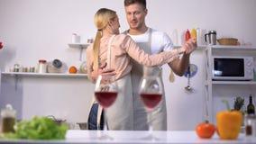 Vetri di vino rosso sulla tavola, coppia romantica che balla sul fondo in cucina stock footage