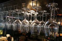 Vetri di vino vuoti che appendono sullo scaffale nella barra Immagini Stock