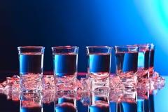 Vetri di vodka con ghiaccio su una tavola di vetro fotografie stock