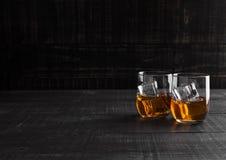 Vetri di whiskey con ghiaccio su fondo di legno Fotografie Stock