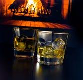 Vetri di whiskey con i cubetti di ghiaccio davanti al camino Immagine Stock
