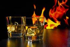 Vetri di whiskey con i cubetti di ghiaccio davanti alla fiamma Immagini Stock