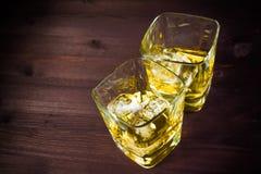 Vetri di whiskey sul vecchio fondo di legno della tavola Fotografie Stock Libere da Diritti
