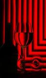 Vetri e bottiglia di vino su colore rosso Fotografia Stock Libera da Diritti