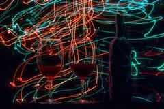 Vetri e bottiglia di vino su fondo e sulle tracce neri Fotografia Stock Libera da Diritti