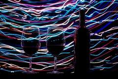Vetri e bottiglia di vino su fondo e sulle tracce neri Fotografie Stock