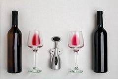 Vetri e bottiglie di vino rosso e bianco su fondo bianco dalla vista superiore Fotografie Stock Libere da Diritti