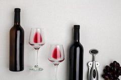 Vetri e bottiglie di vino rosso e bianco su fondo bianco dalla vista superiore Immagine Stock Libera da Diritti