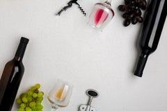 Vetri e bottiglie di vino rosso e bianco su fondo bianco dalla vista superiore Fotografie Stock