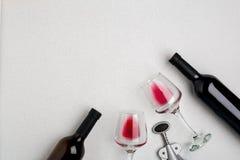 Vetri e bottiglie di vino rosso e bianco su fondo bianco dalla vista superiore Fotografia Stock