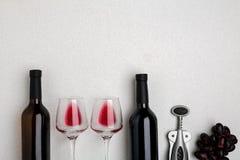 Vetri e bottiglie di vino rosso e bianco su fondo bianco dalla vista superiore Immagini Stock