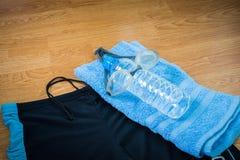 Vetri e costume da bagno, bottiglie di acqua, asciugamano Immagine Stock