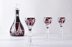 Vetri e decantatore antiquati sulla tavola bianca contro la parete bianca Metta di cristalleria per le bevande aclcoholic immagine stock libera da diritti