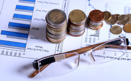 Vetri e monete sui grafici finanziari Immagine Stock Libera da Diritti