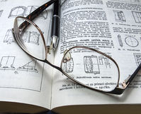 Vetri e penna su un libro Fotografie Stock Libere da Diritti