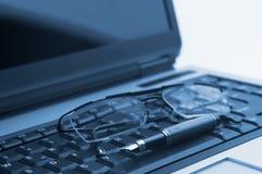 Vetri e penna sul computer portatile Fotografia Stock Libera da Diritti