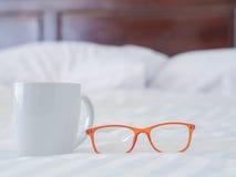 Vetri e tazza bianca sul letto Fotografia Stock