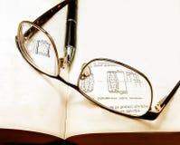 Vetri e una penna su un libro Fotografie Stock
