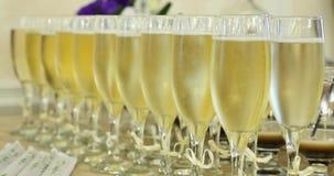 Vetri eleganti con champagne che sta in una fila sulla tavola del servizio durante il partito o la celebrazione stock footage