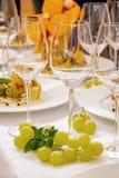 Vetri festivi della tavola per Champagne e l'uva fotografia stock libera da diritti