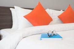 Vetri moderni sulla copertina di libro blu con il letto bianco in camera da letto fotografie stock libere da diritti