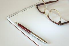 Vetri, penna e blocco note Fotografia Stock