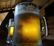 Vetri pieni di birra sullo scrittorio della barra alla barra stile country Fotografia Stock
