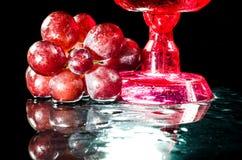 Vetri primo piano dell'uva e del vino rosso un fondo nero Immagini Stock