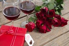 Vetri, regalo e rose del vino rosso su superficie di legno Fotografia Stock