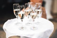 Vetri serventi del cameriere con champagne su un vassoio fotografia stock